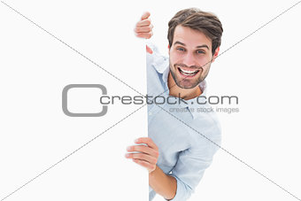 Attractive young man smiling and holding poster