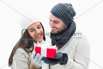 Attractive young couple in warm clothes holding gift