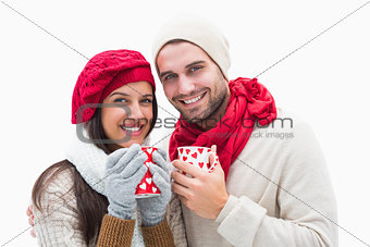 Attractive young couple in warm clothes holding mugs