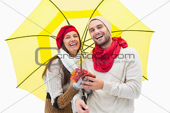 Attractive young couple in warm clothes holding umbrella and leaves