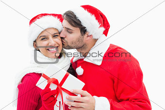 Attractive festive man giving girlfriend a kiss and present