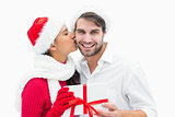 Attractive festive woman giving boyfriend a kiss and present