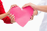 Couples hands holding pink heart