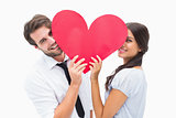 Couple smiling at camera holding a heart