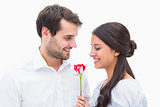 Handsome man offering his girlfriend a rose