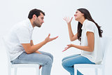 Couple sitting on chairs arguing