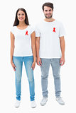 Attractive young couple wearing aids awareness ribbons
