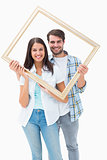 Happy young couple holding picture frame