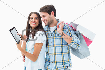 Attractive young couple with shopping bags and tablet pc