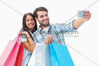 Attractive young couple with shopping bags taking a selfie
