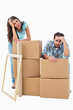 Stressed young couple with moving boxes