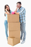 Happy young couple with moving boxes and piggy bank