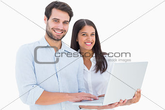 Attractive young couple holding their laptop