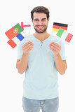 Handsome man holding various european flags