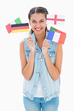 Pretty brunette holding various european flags