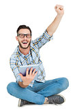 Handsome hipster using tablet pc and cheering