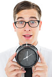Geeky businessman holding alarm clock