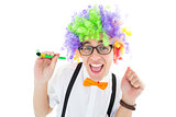 Geeky hipster wearing a rainbow wig holding party horn