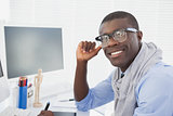 Hipster businessman smiling at camera at his desk