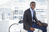 Smiling businessman with his bicycle
