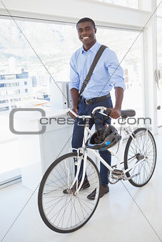 Happy businessman standing with his bike