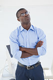 Thoughtful businessman standing with arms crossed