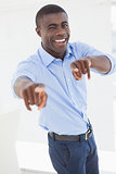 Happy businessman pointing at camera
