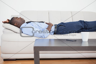Tired businessman lying on the sofa