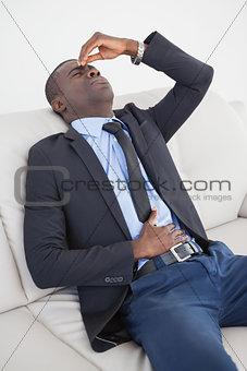 Tired businessman getting headache on the sofa