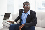Hipster businessman sitting on couch with laptop
