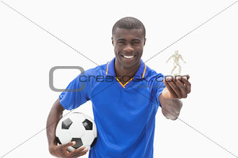 Football player in blue holding ball and figurine