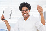 Happy businessman showing notepad and thumbs up