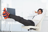 Businessman relaxing in his swivel chair with feet up