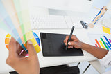 Designer working at desk using digitizer and colour sample