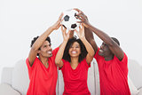 Football fans sitting on couch holding ball