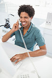 Handsome businessman talking on phone at desk