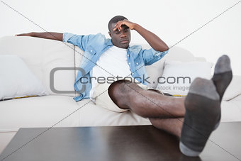 Casual man sitting on sofa with feet up