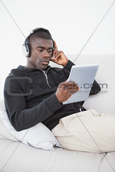 Casual man sitting on his sofa listening to music on tablet pc