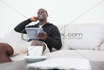 Casual man sitting on sofa enjoying music on his tablet pc