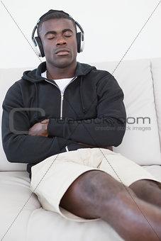 Casual man sitting on sofa enjoying music with eyes closed