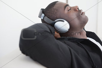 Casual man sitting on sofa enjoying music with eyes closed