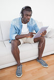 Casual man sitting on sofa using his tablet pc to listen to music