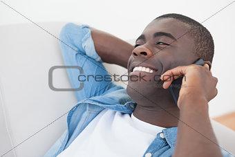 Casual man lying on sofa talking on phone