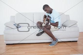 Casual man sitting on sofa playing the guitar with tablet pc