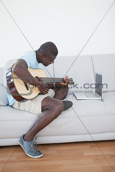 Casual man sitting on sofa playing the guitar