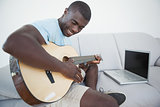 Casual man sitting on sofa playing the guitar with laptop