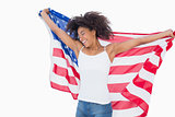 Pretty girl wrapped in american flag cheering