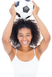 Pretty girl with afro hairstyle smiling at camera holding football