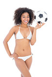 Athletic girl in white bikini holding football