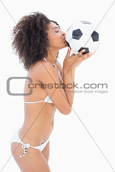 Athletic girl in white bikini kissing football